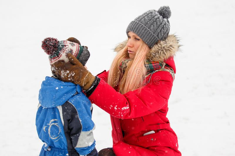 Photo of mother correcting her son`s hat in winter park royalty free stock photos