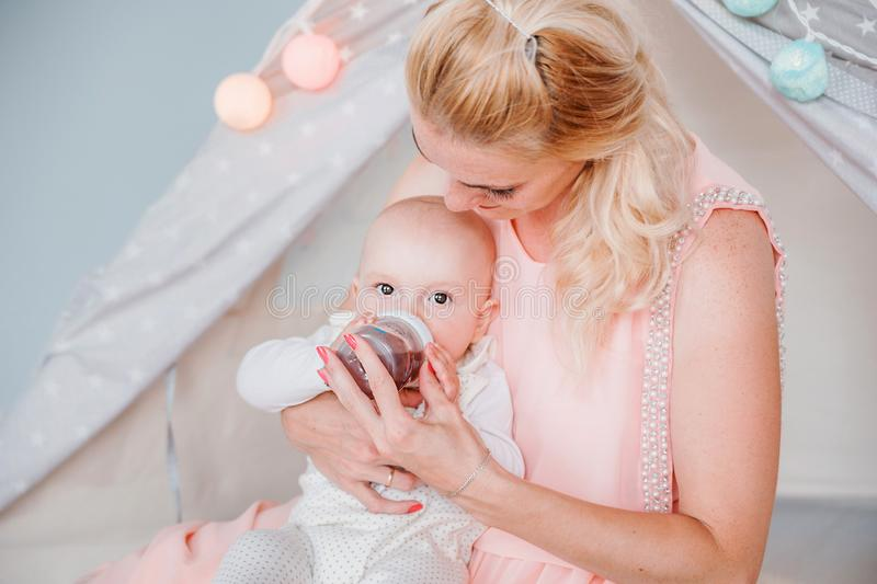 Mother feeds her son from a bottle in a room near a children`s tent. Photo of mother feeds her son from a bottle in a room near a children`s tent royalty free stock photo