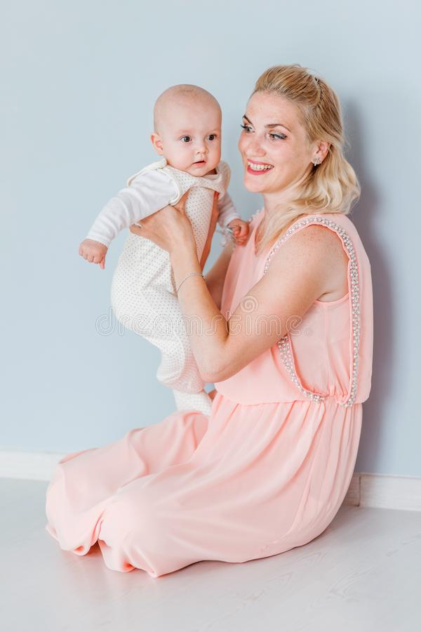 Mother in a pink dress holds a little son in her arms and smile. Photo of mother in a pink dress holds a little son in her arms and smile stock photo