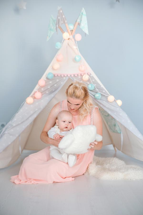 Mother plays with her son in a room near a children`s tent. Photo of mother plays with her son in a room near a children`s tent stock image