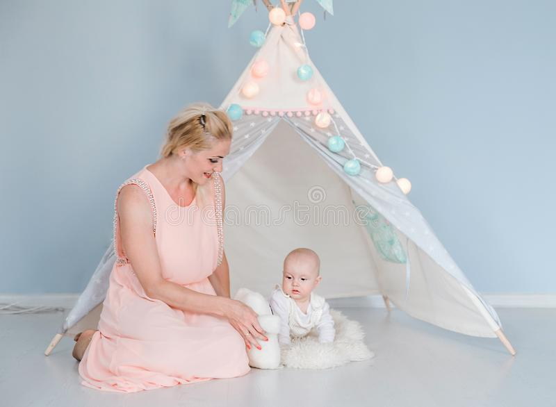 Mother plays with her son in a room near a children`s tent. Photo of mother plays with her son in a room near a children`s tent stock photography