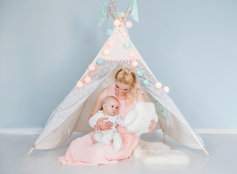 Mother plays with her son in a room near a children`s tent. Photo of mother plays with her son in a room near a children`s tent royalty free stock image