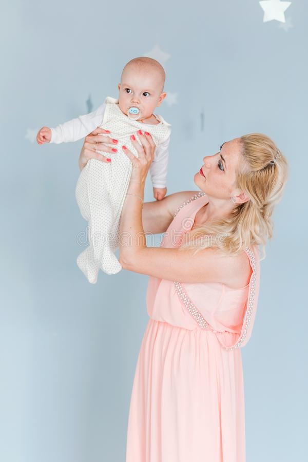 Mother plays and throws up a child in the children`s room against the background of the blue wall. Photo of mother plays and throws up a child in the children`s royalty free stock image
