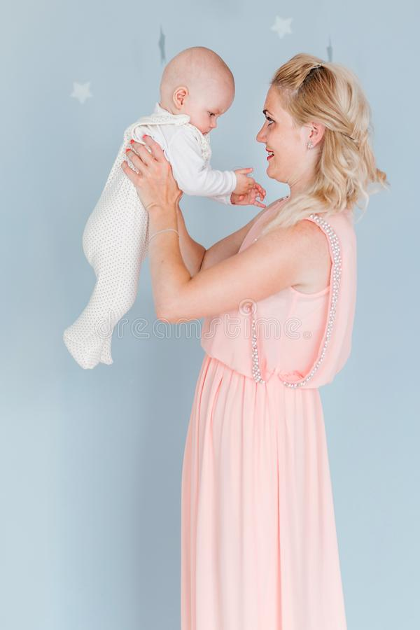 Mother plays and throws up a child in the children`s room against the background of the blue wall. Photo of mother plays and throws up a child in the children`s stock photos