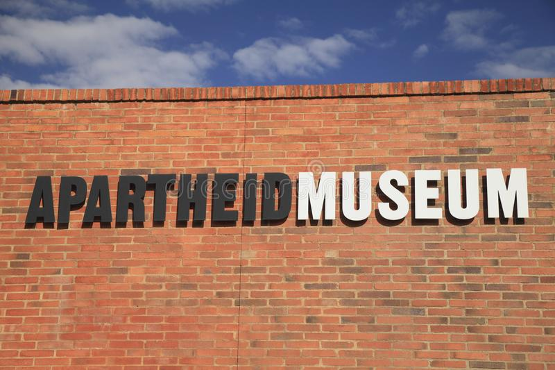 Johannesburg. The Museum of Apartheid. Wall. Photo of the name of the apartheid museum on a wall of red brick against a blue sky with clouds on a sunny stock photo