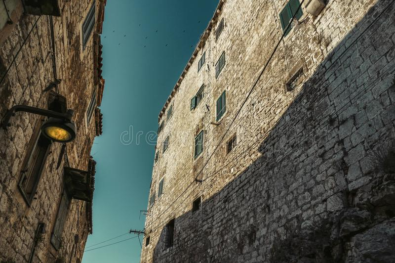 Photo of narrow street from down in Sibenik croatia with flock of birds above the walls. Historical houses on street with lamp stock photography