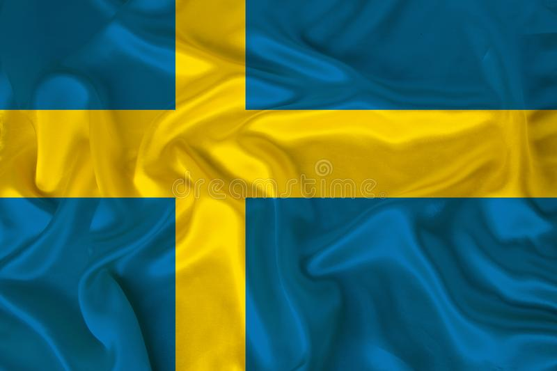 Photo of the national flag of the state of Sweden on a luxurious texture of satin, silk with waves, folds and highlights, close-up royalty free stock photography