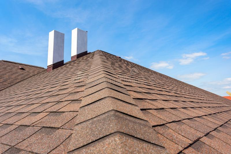 Asphalt tile roof with chimney on new home under construction stock photography
