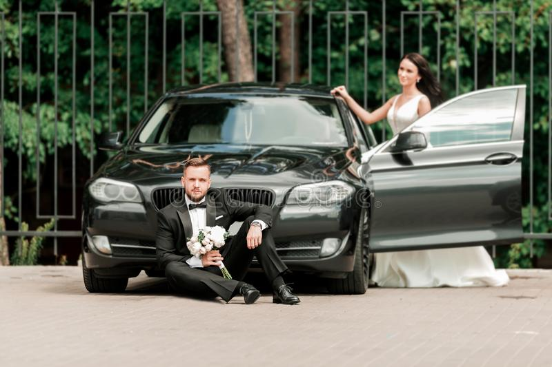 Photo newlyweds on a walk near their cars. royalty free stock photo