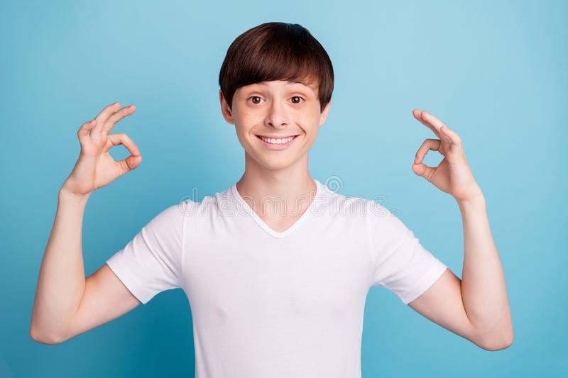 Photo of nice cheerful funny interesting boy showing you how his choice is perfect while isolated with blue background stock photos