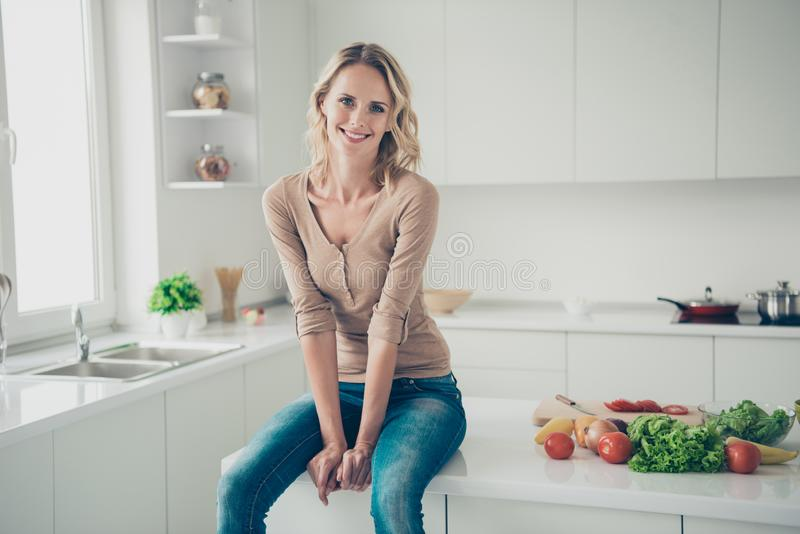 Photo of nice-looking good-dressed blond hair lady with her whit. E hollywood smile she sit on table inside cozy comfort apartment look at camera royalty free stock photography
