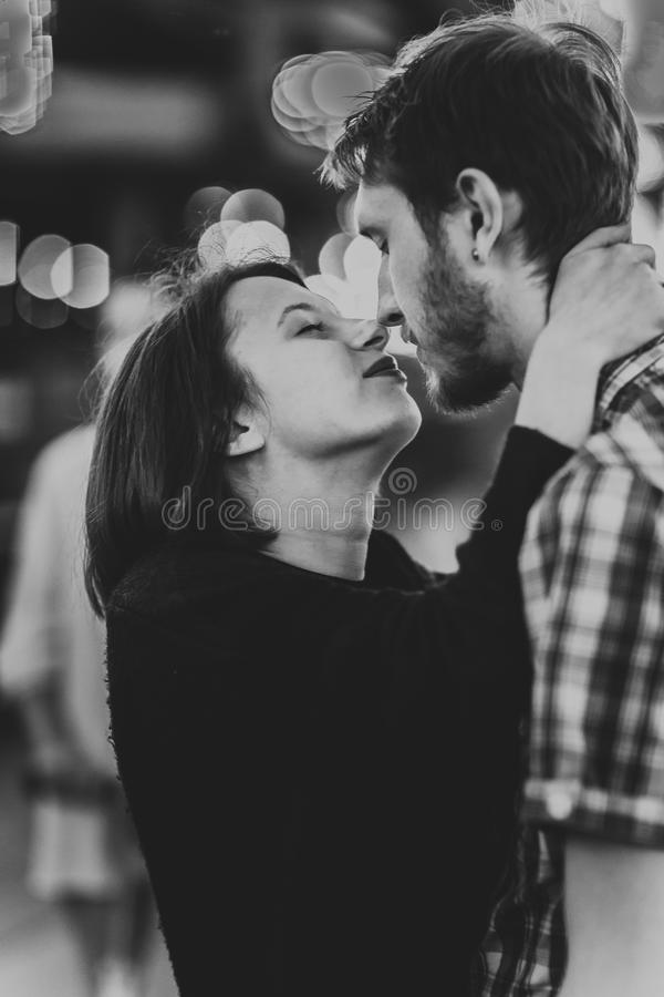 Photo noire et blanche d'un couple heureux embrassant des baisers le soir sur les guirlandes légères images libres de droits