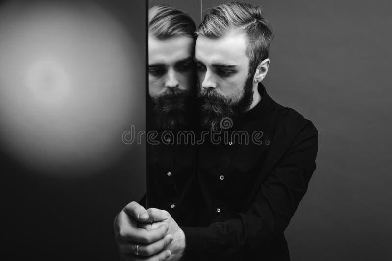 Photo noire et blanche d'un homme avec une barbe et une coiffure élégante habillées dans la position noire de chemise à côté du m photos stock