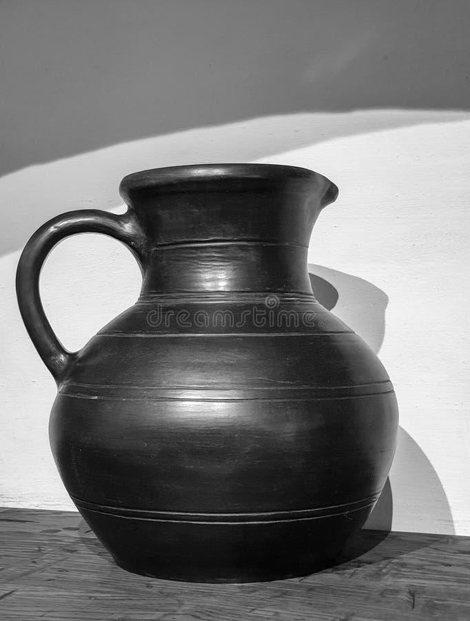 Photo noire et blanche d'une cruche antique d'argile avec avec l'ombre sur un dessus de table en bois image stock