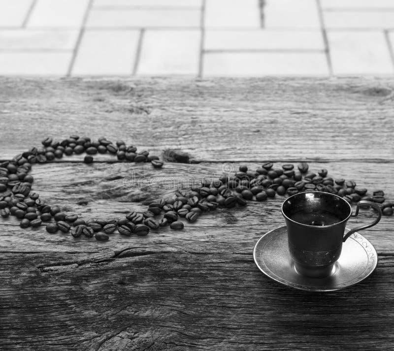 Photo noire et blanche d'une tasse argentée d'expresso et des grains de café sur la table en bois image libre de droits