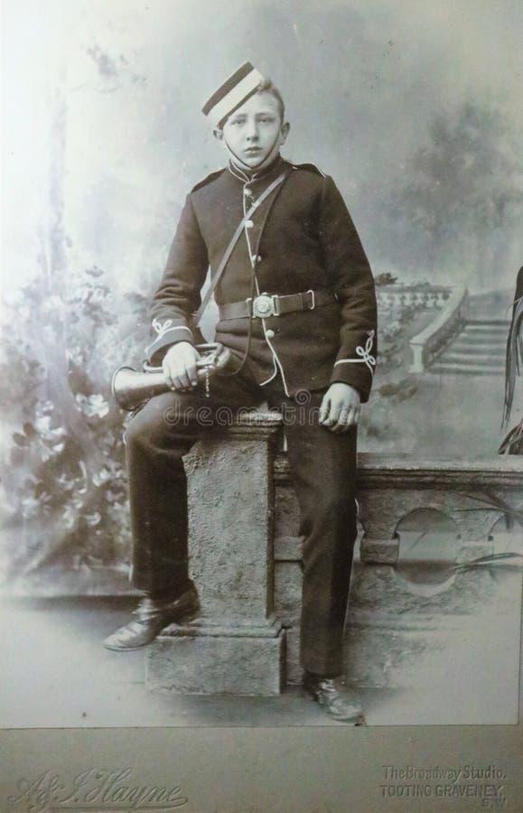 Photo noire et blanche de cru d'un jeune garçon dans l'uniforme militaire tenant une bugle photos stock