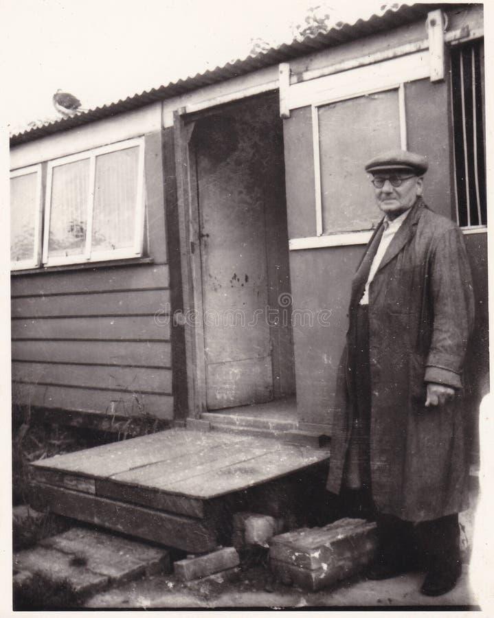 Photo noire et blanche de cru de vieil homme utilisant un chapeau devant les années 1940 jetées ? photos stock
