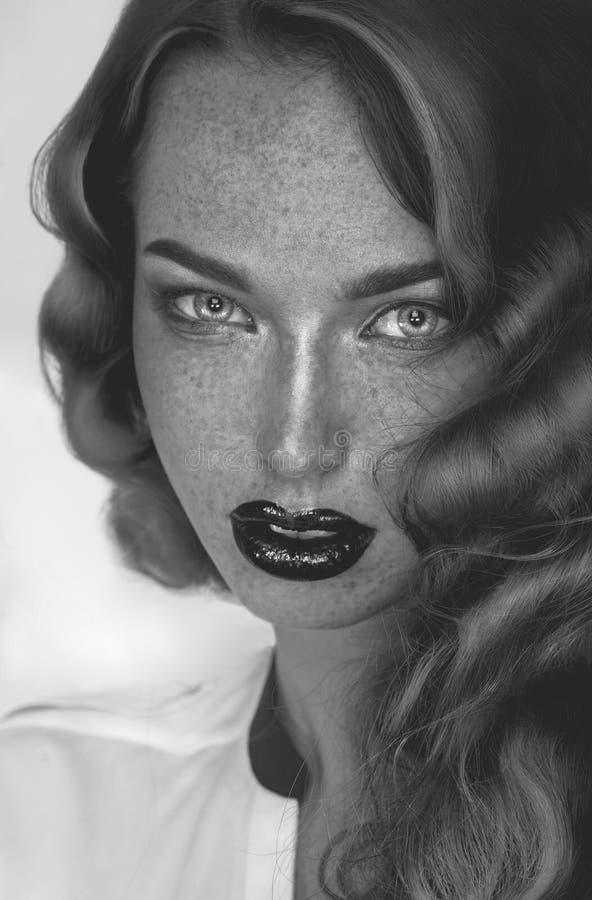 Photo noire et blanche de fille séduisante avec des taches de rousseur regardant image stock