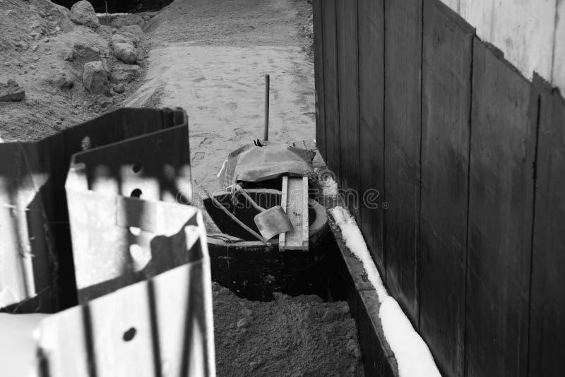 Photo noire et blanche du chantier de construction, installation de l'anneau pour le puits photographie stock