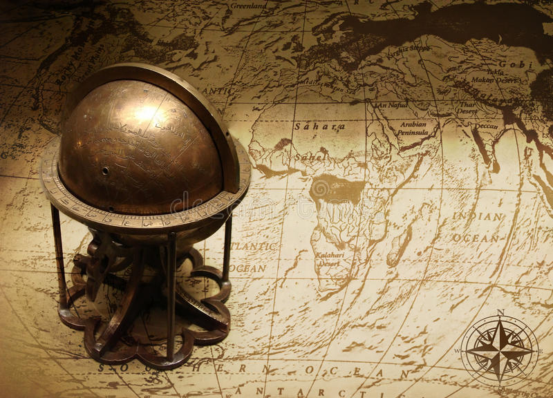 Old globe on map of the world. Photo of old globe on vintage world map stock image