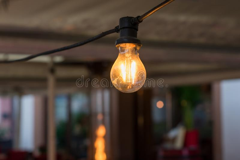 One old light bulb on a fragment of a garland that glows with a warm yellow light. Photo of one old light bulb on a fragment of a garland that glows with a warm royalty free stock photos