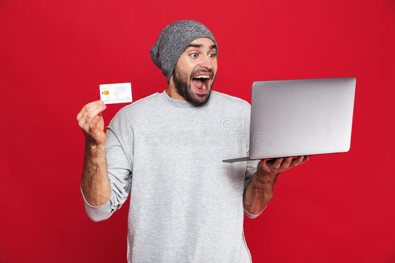 Photo of optimistic guy holding credit card and silver laptop isolated over red background royalty free stock photo