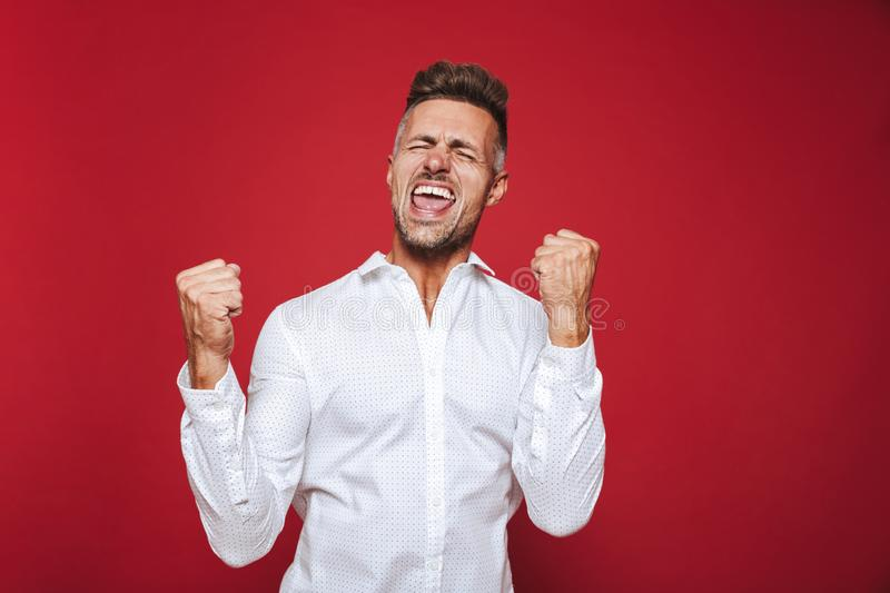 Photo of optimistic man in formal wear shouting and clenching fists, isolated over red background stock photo