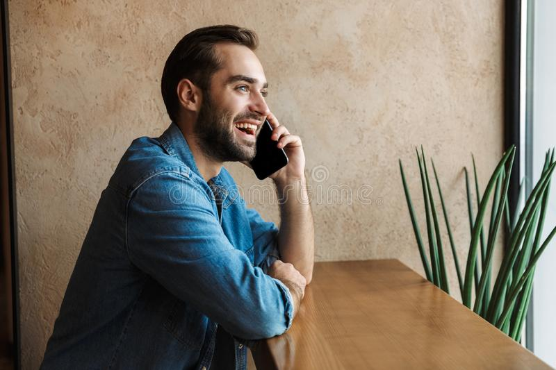 Photo of optimistic young man smiling and talking on cellphone while sitting on chair in cafe indoors royalty free stock images