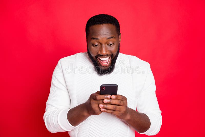 Photo of overjoyed dark skin man holding telephone hands reading new x-mas comments in blog wear white knitted sweater. Photo of overjoyed dark skin man holding royalty free stock images