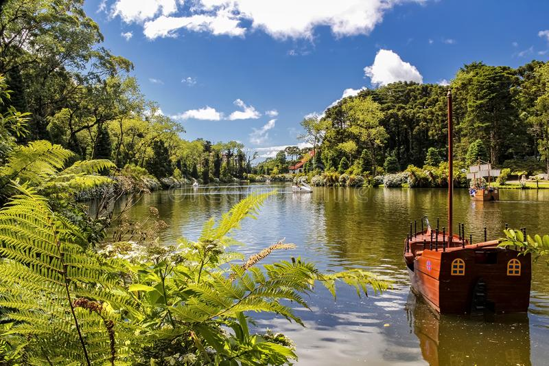 Paddle boat on the Black Lake of Gramado city, Rio Grande do Sul - Brazil, on a sunny day with sky with clouds. Photo of Paddle boat on the Black Lake of Gramado royalty free stock images