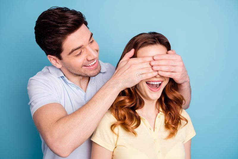 Photo of pair excited bonding romance moment hide eyes do not look guess who wear casual t-shirts isolated blue. Photo of pair excited bonding, romance moment stock image