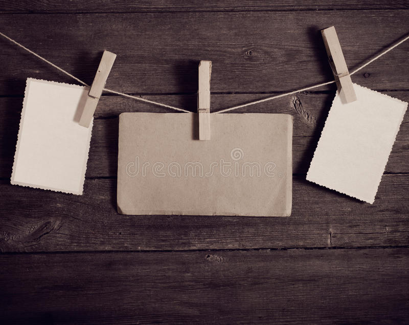 Photo paper attach to rope with clothes pins. On wooden background royalty free stock photography
