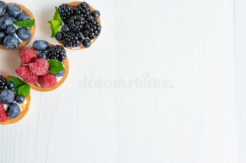 Photo pattern with tartlets on a white wooden background. Cakes with berries of marina, blueberry, blueberry with mint. Leaves. Photo patern with sweets top stock image