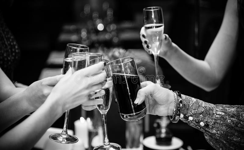 Photo of people holding glasses of wine and clinking royalty free stock images