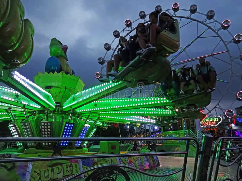 Amusement Park Rides in Barcelona Spain. Photo of people riding an amusement park ride in barcelona spain on 9/24/18. The ferris wheel is in the background stock image