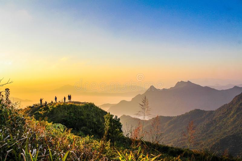Photo of People Standing on Top of Mountain Near Grasses Facing Mountains during Golden Hours stock images