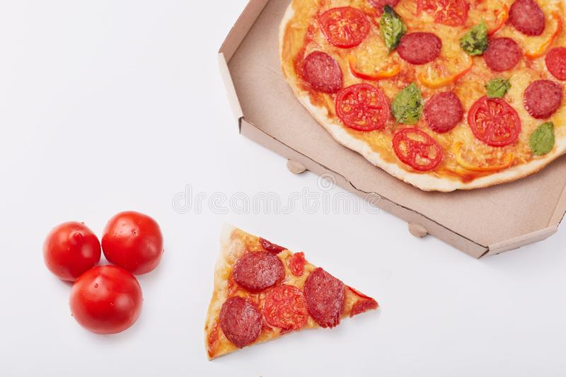 Photo of pepperoni pizza with mozzarella cheese, salami, pepper, spices and fresh spinach, cardboard box, piece of pizza and three stock photography