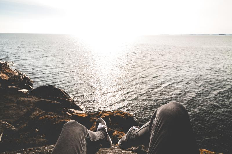 Photo of Person Sitting on Cliff royalty free stock photos