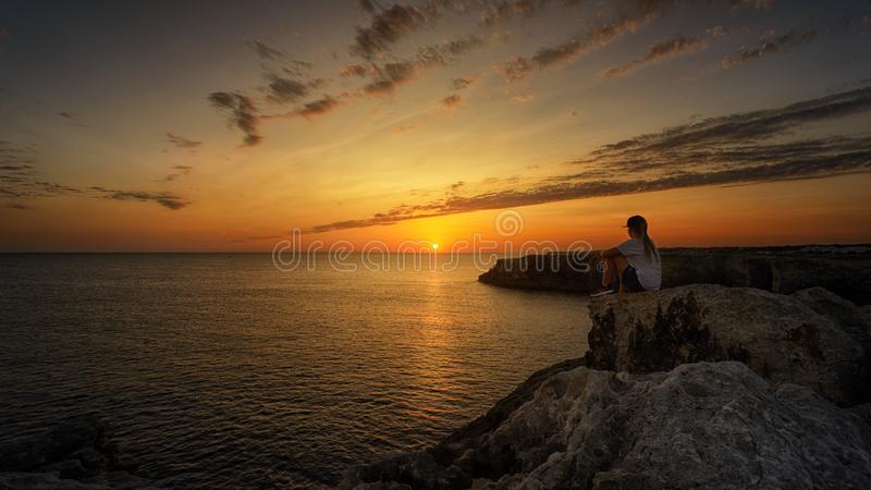 Photo of Person Sitting on Rock During Sunset royalty free stock photography