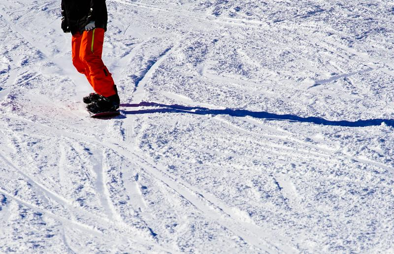 Photo of Person Wearing Black Top and Orange Pants Riding Snowboard royalty free stock image