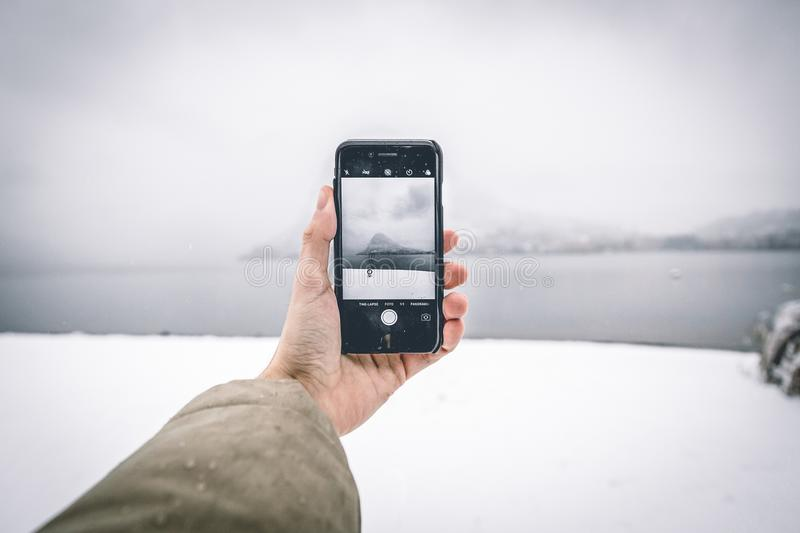 Photo of Person Wearing Brown Coat Holding Android Smartphone While Taking Picture of Mountain and Body of Water royalty free stock image