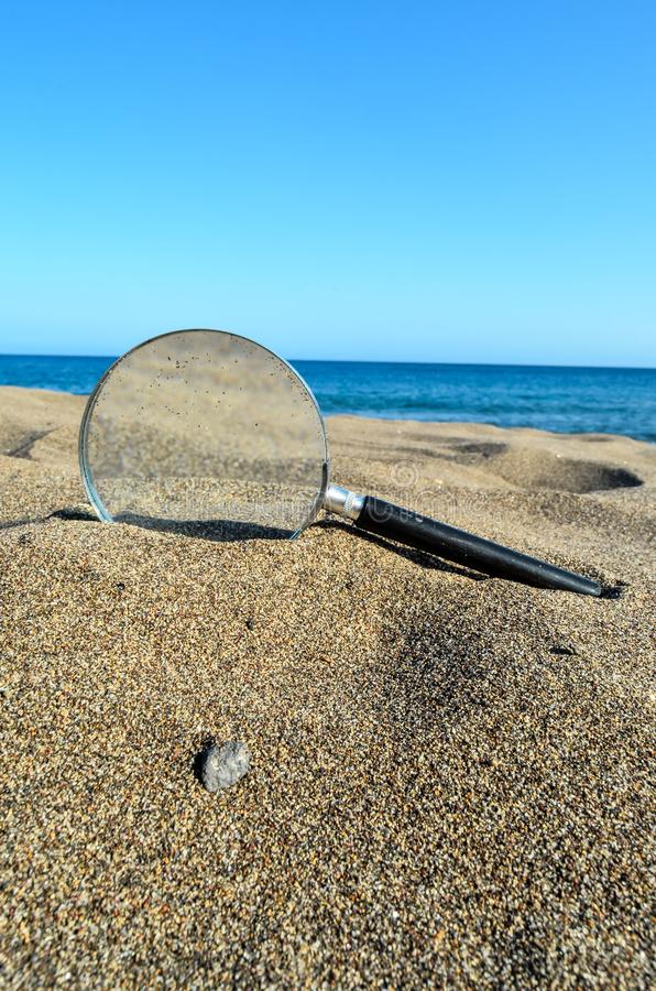 Magnify Glass on the Sand Beach. Photo Picture of a Loupe Magnify Glass on the Sand Beach royalty free stock photography