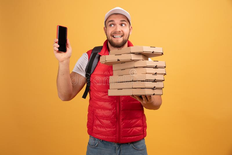 Photo of pizza man receives orders from customers via smart phone, holds many carton boxes with fast food, has unpleasant look to. Speak with dissatisfied royalty free stock photography