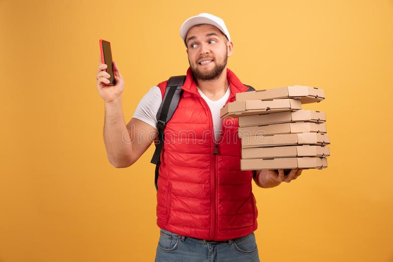 Photo of pizza man receives orders from customers via smart phone, holds many carton boxes with fast food, has unpleasant look to. Speak with dissatisfied royalty free stock photo