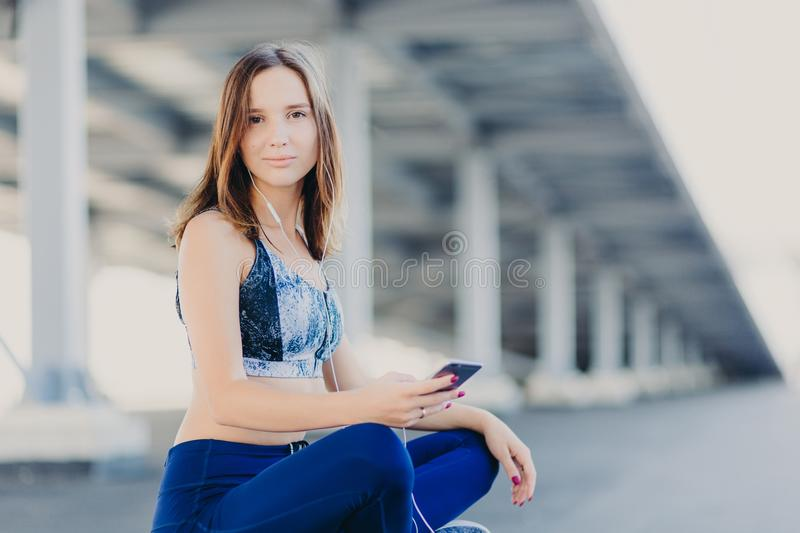 Photo of pleasant looking attractive sporty woman sits crossed legs, dressed in top and leggings, holds modern cell phone, enjoys royalty free stock photos