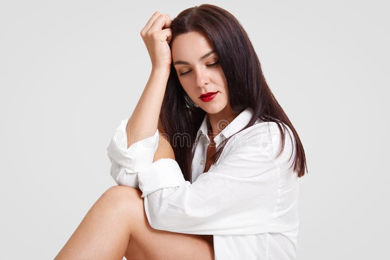 Photo of pleasant looking brunette female with red painted lips, dark hair, slender legs, leans on hand, focused down, poses for f royalty free stock photography