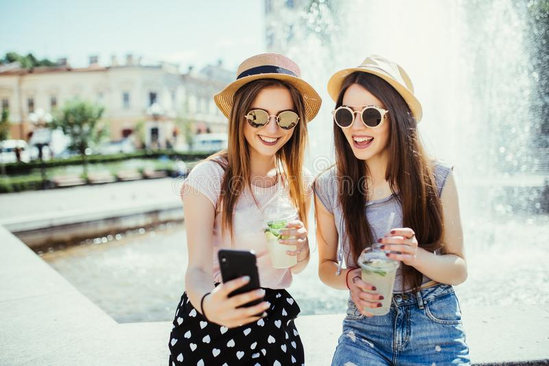 Photo of pleased two mixed race women get good news on mobile phone, recieve email or make selfie with smart phone, drink fresh co stock image