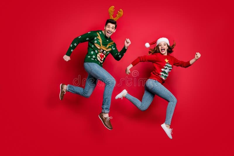Photo pleine longueur d'un couple de saut fou excité par les prix de mas x-mas des rabais porter des cavaliers de vilains ornemen photo libre de droits