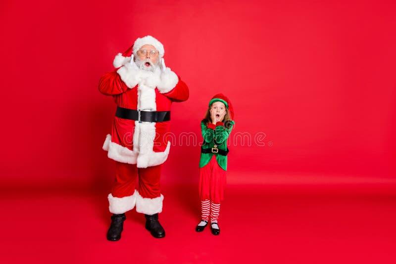 Photo pleine longueur de l'impressionnant elfe de santa claus en chapeau avec lunettes voir la magie de noël cri omg toucher photo libre de droits
