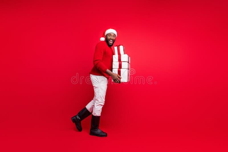 Photo pleine longueur du joyeux promoteur tenant des paquets avec du ruban pour la nuit de noël portant le chapeau de santa claus images stock